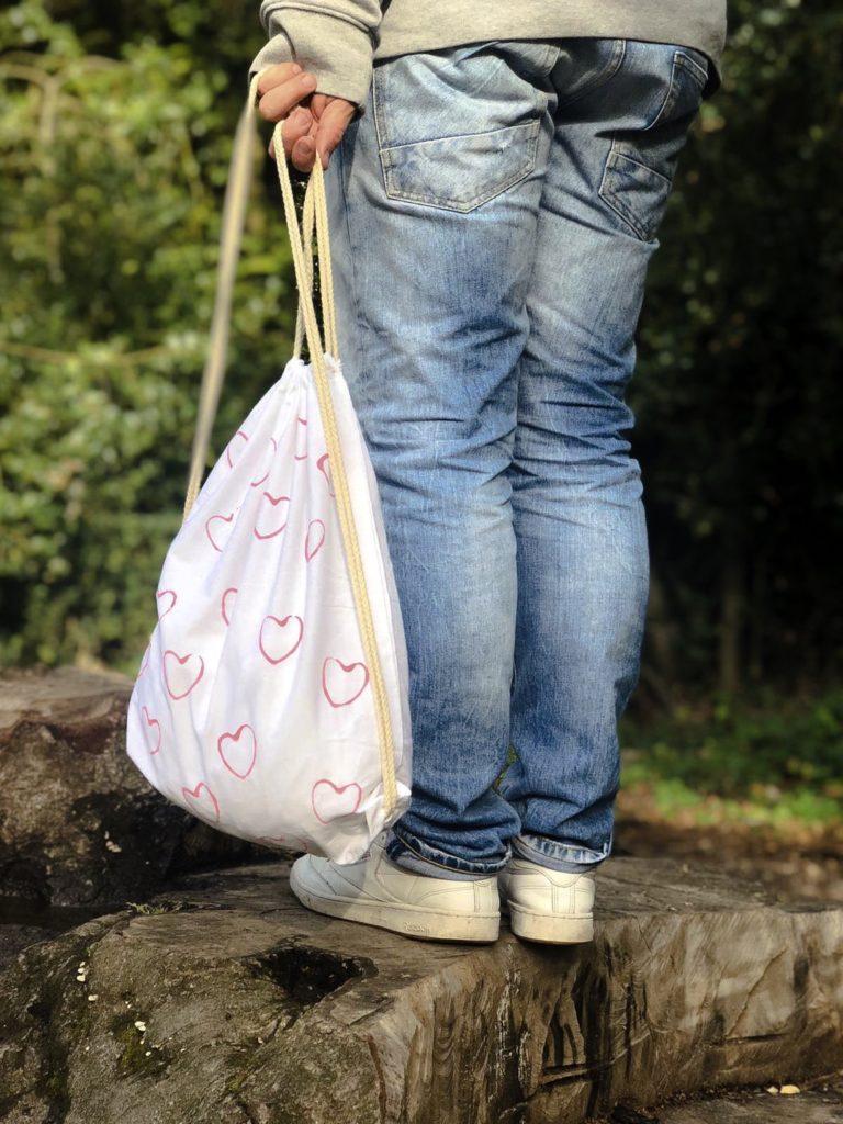 Eine Bastelidee für kleine Kinder: Mit Toilettenpapierrollen Herzen auf Turnbeutel stempeln.
